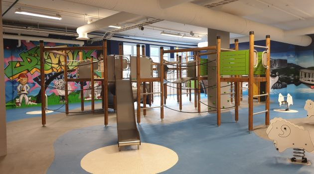 Indoor playground area with a climbing frame and slide.
