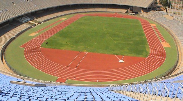 Showing a red running track with grass square in the middle. Image has been taken at the top of an outdoor stadium which has blue seats.