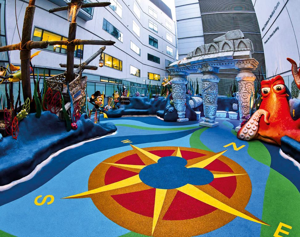 A colourful safe playground area in an enclosed outdoors space. The playground resembles an under the sea landscape with a sunken ship, a large octopus and a compass all made from Conica's rubber mulch. This image helps show the wide range of colours that rubber mulch can be made into.