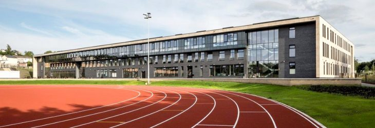 Looking onto a bend on a red athletics running track. The running track is set in the front of a large school building and is surrounded by grass.