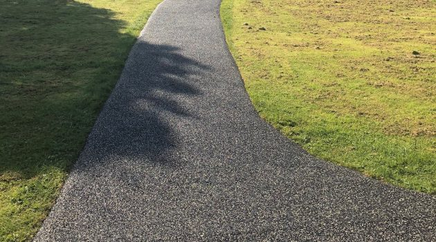 Pathway across a green field.