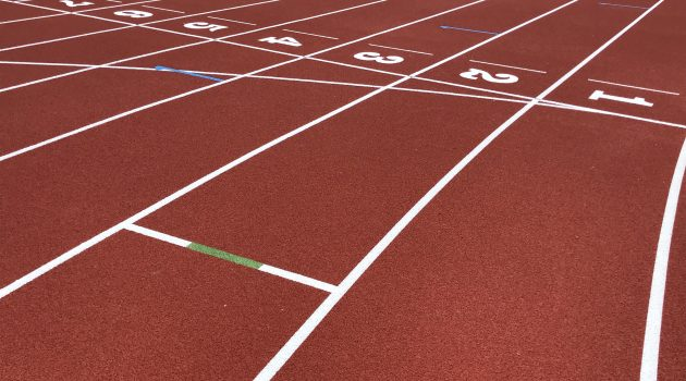 Close up of a red running track with the lane numbers shown.