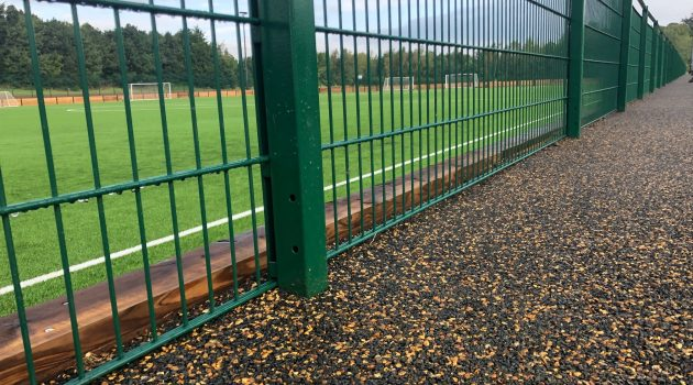 Path next to a green fence that's enclosing a grass football pitch.