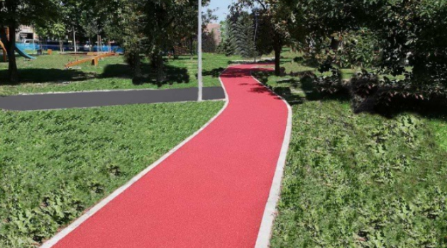 Red pathway track running through a park with green bushes on both sides.