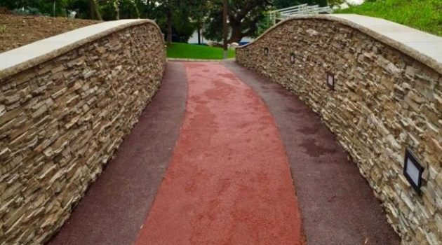 Red pathway running over a yellow stoned bridge.