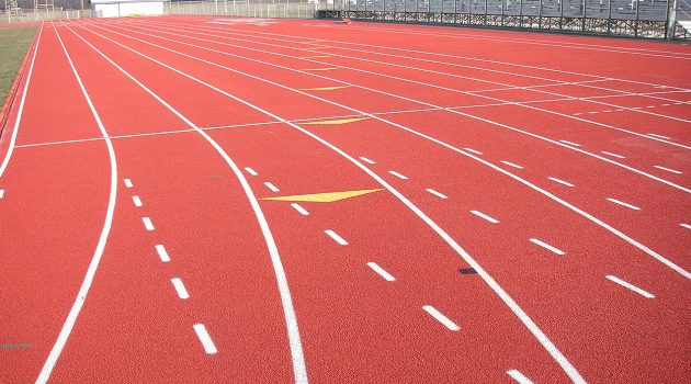 Red running track with white lines.