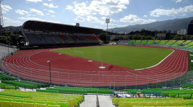Looking onto an athletics stadium from the the stands. The track in red with white line and features a grass area in the middle.