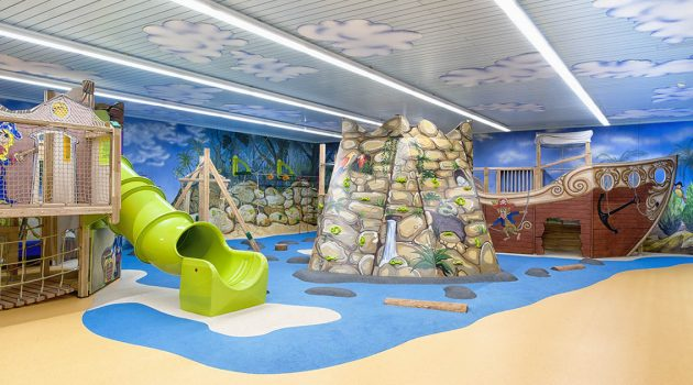 Indoor playground area with a green tunnel slide and climbing frame.